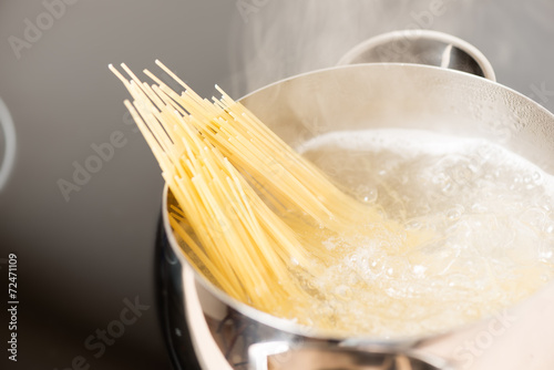Fotografering  Pan with spaghetti cooking in boiling water