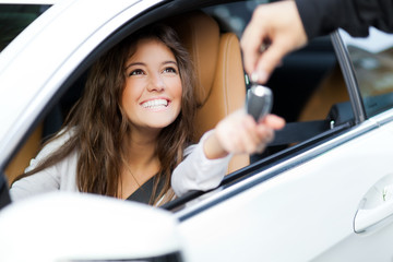 Woman receiving keys of her new car from dealer