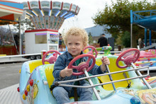 A Little Boy Playing In A Fun Fair Carousel