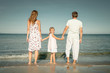 Happy family standing at the beach at the day time