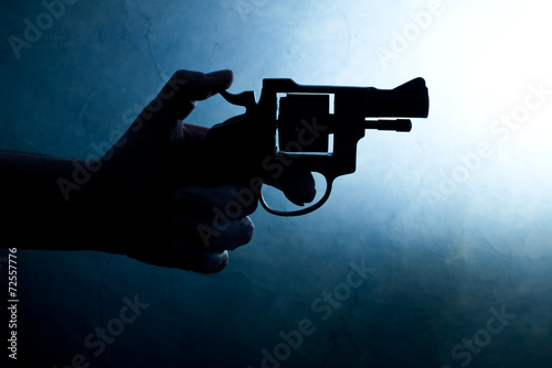 Fototapeta  Silhouette of a mans hand with a handgun