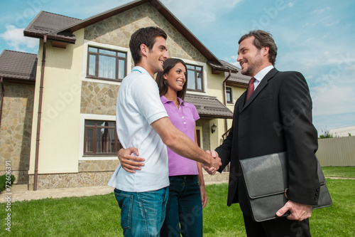 Photo  Salesman shaking hands with property owners.