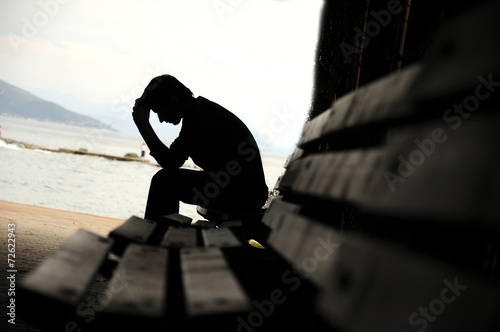 Photo depressed young man sitting on the bench