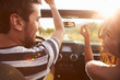 canvas print picture - Young Couple Driving Along Country Road In Open Top Car