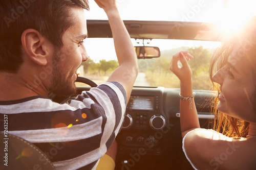 Fotografiet  Young Couple Driving Along Country Road In Open Top Car