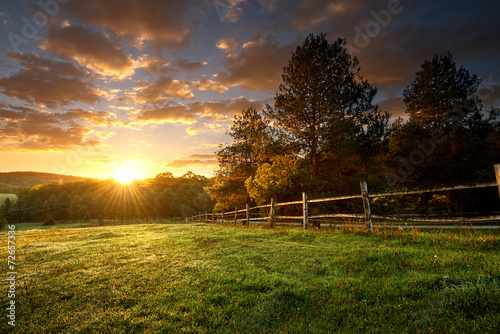 Fotografiet  Picturesque landscape, fenced ranch at sunrise