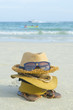 Summer beach bag with straw hat,towel,sunglasse s and flip flops on sandy beac