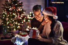 Portrait Of A Young Couple In Their Living Room In  Christmas Ev