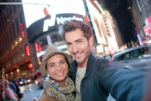 Plagát  Couple standing in Time Square quarter by night