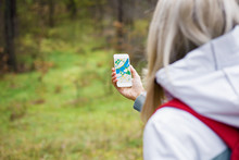 Woman Geocaching In Forest And Using Mobile App