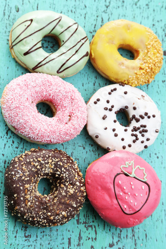Deurstickers Dessert Delicious donuts with glaze on colorful wooden background