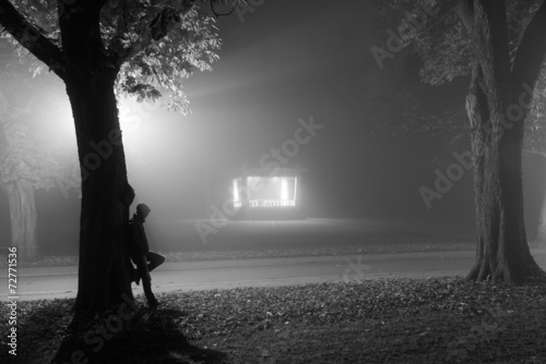 Fotografia  Man leaning agianst a tree in a foggy park at night.