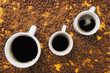 Three cups of coffee on coffee beans background