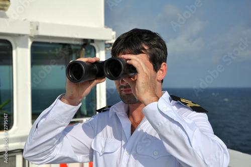 Fényképezés  navigator on navigation bridge during his watch  with binocular