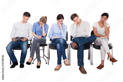 Bored Businesspeople Sitting On Chairs