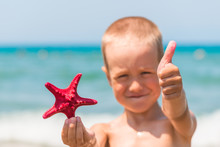 Cheerful And Happy Boy With Starfish On The Beach