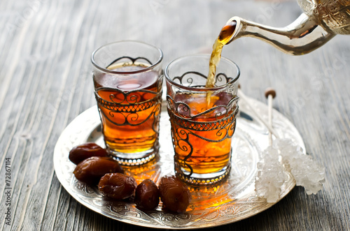 Fotografia  Traditional arabic tea with dates and sugar on a plate