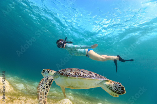 Foto Young girl snorkeling with sea turtle