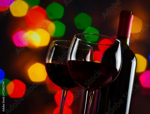 red wine glasses near bottle on colorful bokeh lights background