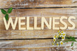 Leinwandbild Motiv Wellness written with wooden letters, chamomile flowers on wood
