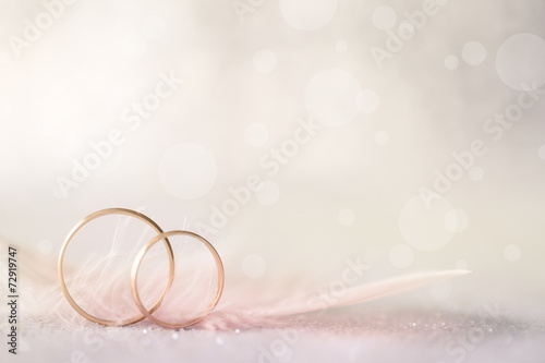 Fotografía  Two Golden Wedding Rings and Feather - light soft background