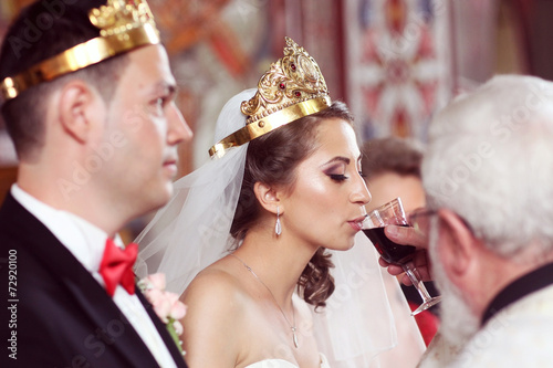 Fotografie, Obraz  bride and groom in church front of priest