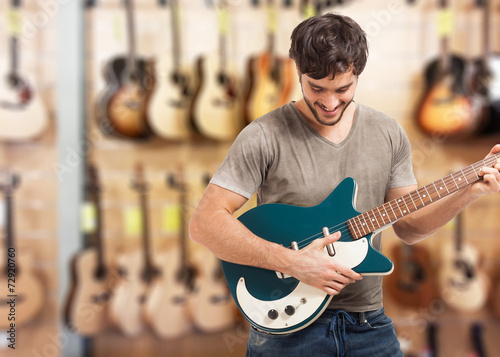 Photo Stands Music store Man testing a guitar in a store