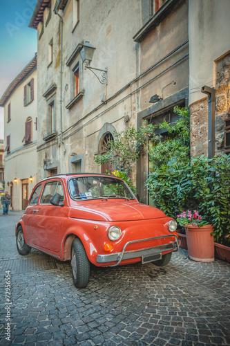 stary-kultowy-czerwony-wloski-samochod-zaparkowany-na-ulicy-przy-restauracji