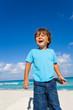 Happy boy stands on sandy beach of ocean coast