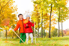 Boy And Girl With Rakes Stand In Autumn Park