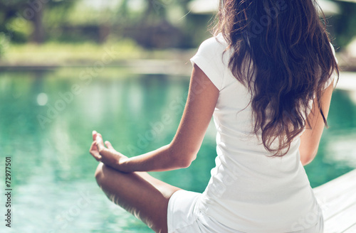 Slim Woman Meditating at the Poolside