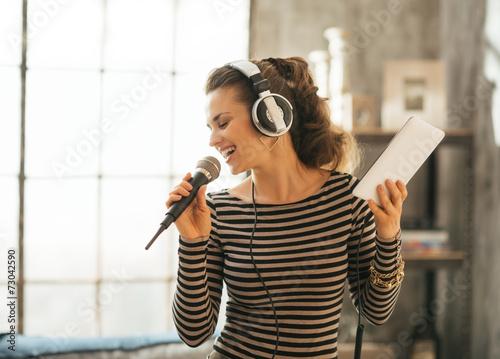 Fotografía Happy young woman singing karaoke in loft apartment