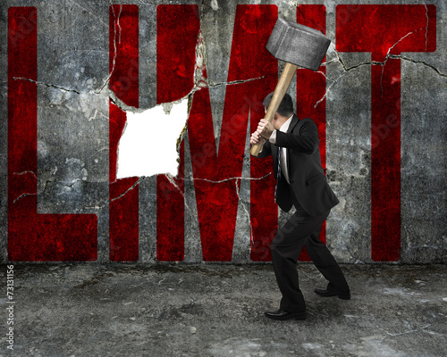 Valokuva  businessman holding sledgehammer hitting red LIMIT word on concr