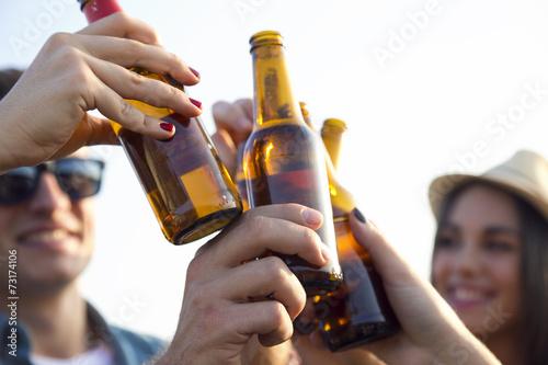 Fotografía  Retrato de grupo de amigos que tuestan con botellas de cerveza.