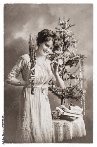 young woman with christmas tree and gifts. antique picture