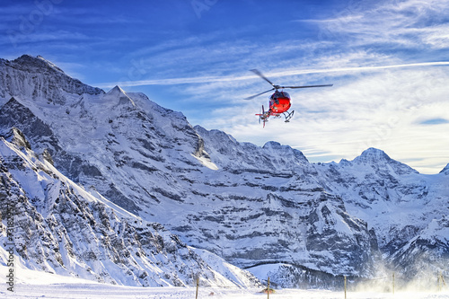 Tuinposter Helicopter Red helicopter flying at swiss alps near Jungfrau mountain