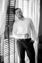 Monochrome Portrait Of Elegant Businessman Leaning Against Windo