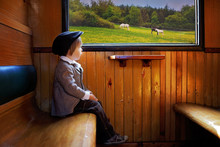Boy, Dressed In Vintage Coat And Hat, Sitting In A Train