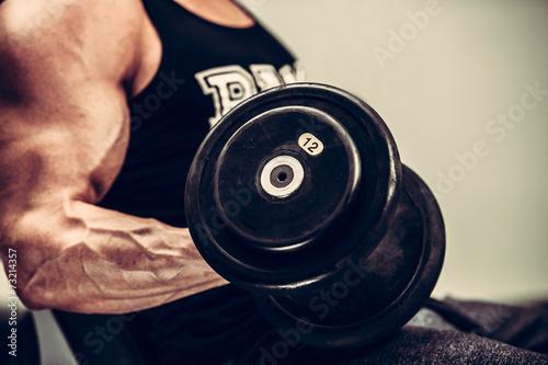 obraz lub plakat Hnadsome młody człowiek pracuje obecnie z hantlami w fitness - Powe