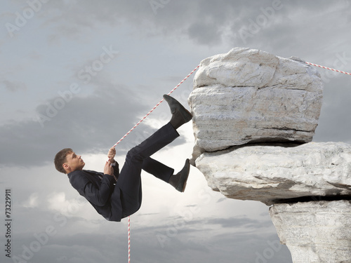 Young businessman scaling a rock Poster