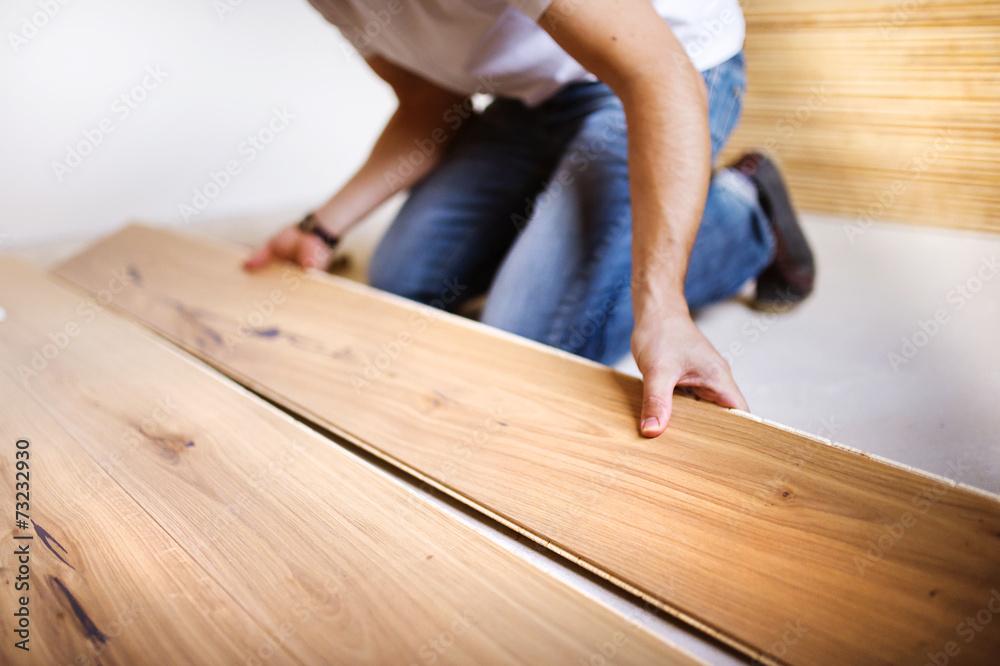Fototapeta Handyman installing wooden floor