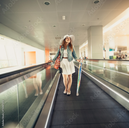 Papiers peints Retro woman in hat with handbag standing on escalator line at airport