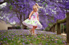 Cute Happy Little Girl In Blooming Park. Beautiful Jacaranda