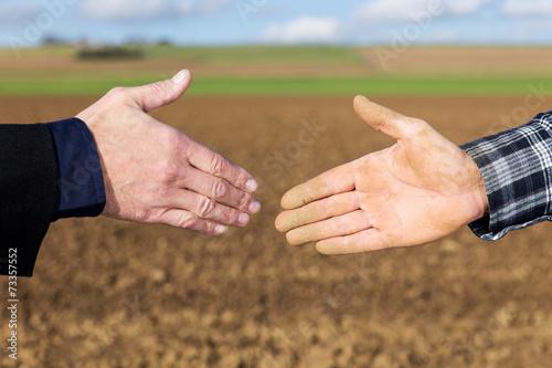 Fotografie, Obraz  Handschlag zwischen Geschäftsmann und Landwirt vor Acker