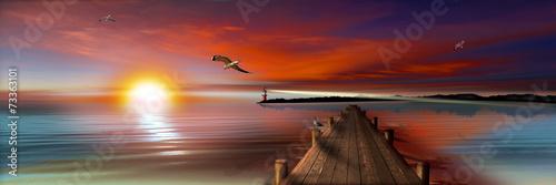 Fotografía Sonnenuntergang am Bootssteg mit Leuchtturm und Möwen