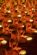 Buddhist monk sculptures with candles at temple in holy day.