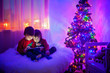 canvas print picture - Two boys, playing on tablet at home, next to christmas tree