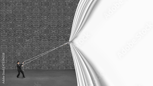 businessman pulling down white curtain covering old dark brick w Canvas Print