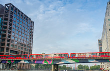 LONDON - AUG 20, 2013: Red Train Crosses River Between Canary Wh