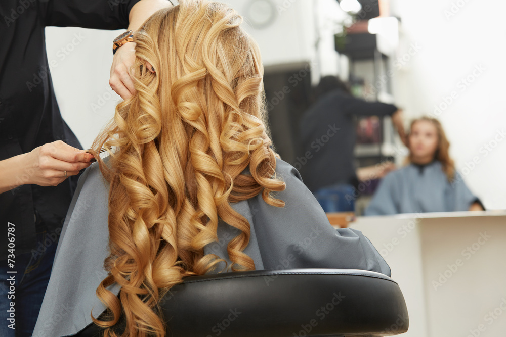 Fototapeta Blonde curly hair. Hairdresser doing hairstyle for young woman i